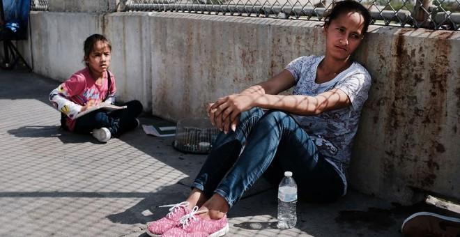 Una mujer hondureña y su hija que huyen de la violencia y la pobreza esperan en la frontera con EEUU tras haberles sido rechazada la entrada. SPENCER PLATT (AFP)