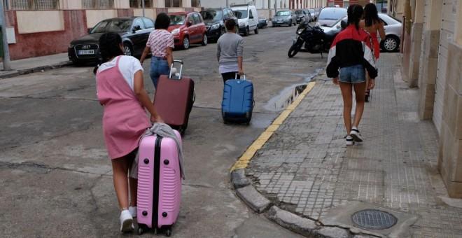 Varias de las menores marroquíes devueltas de Palencia a Melilla cargan con sus maletas en la ciudad autónoma.- JOSÉ PALAZÓN/PRODEIN