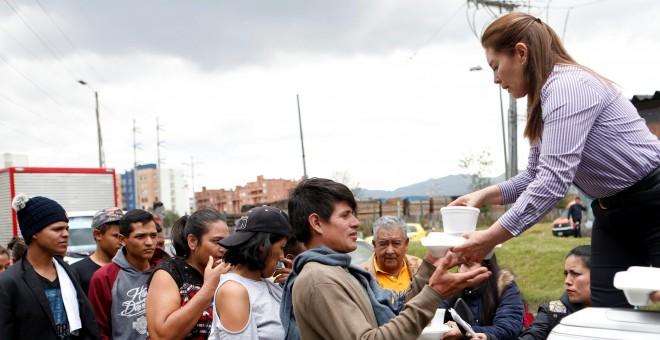 Migrantes venezolanos reciben comida de voluntarios colombianos en la estación de Bogotá, Colombia.- REUTERS/Luisa Gonzalez