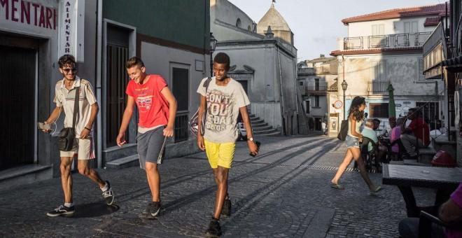 Jóvenes residentes en Riace pasean por unas calles céntricas del pueblo. - G.S.