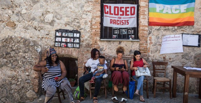 Migrantes y población local en la taberna Donna Rosa, epicentro de las protestas contra la decisión del Gobierno central y la Prefectura de bloquear los fondos. - G.S.