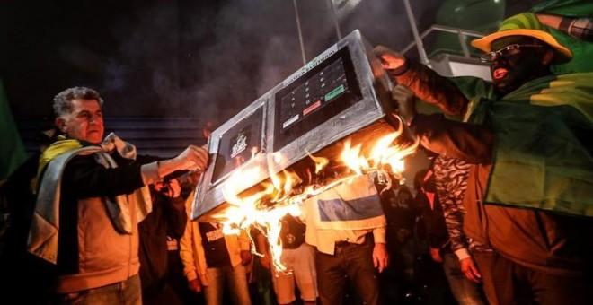 07/10/18.-Simpatizantes del candidato presidencial Jair Bolsonaro del Partido Social Liberal (PSL) se reúnen hoy, domingo 7 de octubre de 2018, y queman una urna electrónica en la avenida Paulista en Sao Paulo (Brasil). El ultraderechista Jair Bolsonaro s
