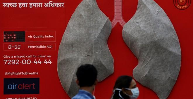 Unas personas pasan junto a un aviso sobre los efectos de la contaminación colocado en el exterior de un hospital en Nueva Delhi. REUTERS/Anushree Fadnavis