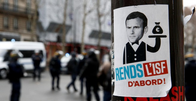 Caricatura de Macron como mayordomo del dinero.- REUTERS