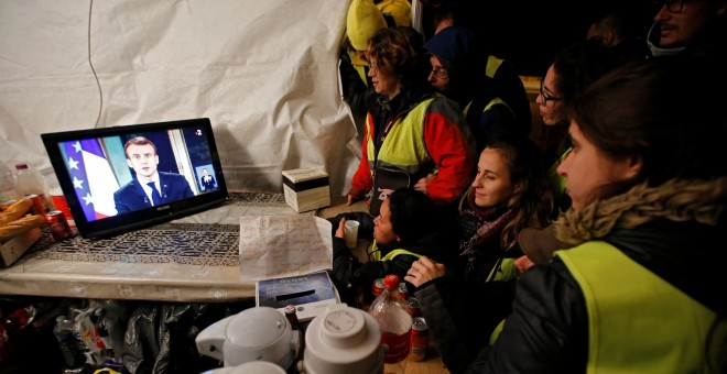 Miembros del movimiento conocido como 'chalecos amarillos' observan el discurso del presidente de Francia, Emmanuel Macron. - EFE