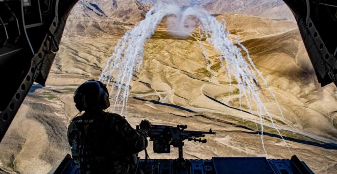 Un soldado del ejército estadounidense sobrevolando Afganistán en helicóptero. / REUTERS