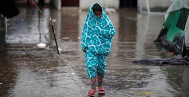 Una niña centroamericana que viaja en una caravana de migrantes, envuelta en una toalla para protegerse de la lluvia en un refugio de Tijuana. / REUTERS - MOHAMMED SALEM