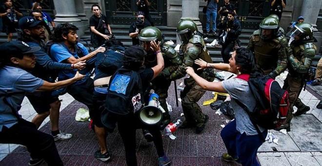 Personas Mapuche y carabineros se enfrentan durante una protesta por el asesinato del comunero mapuche Camilo Catrillanca hoy, en Santiago (Chile). Cientos de personas se dieron cita hoy en la capital chilena para protestar por la muerte del comunero mapu