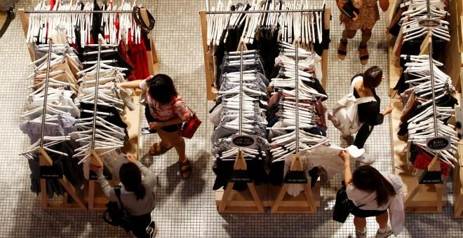 Un grupo de mujeres echan un vistazo a varios conjuntos de ropa en una tienda de un centro comercial de Sidney. REUTERS/Daniel Munoz