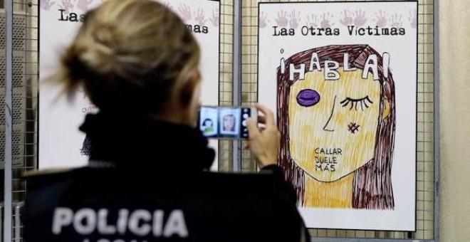 Una agente de la Policía Local fotografía un cartel contra la violencia machista. / EFE