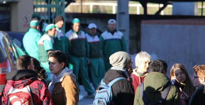 Al fondo, varios trabajadores del matadero de Getafe observan a un grupo de animalistas que se concentra a las puertas del centro para realizar una vigilia vegana./ Alejandro Tena