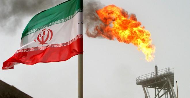 Un bandera de Irán cerca de una llamarada de gas en una plataforma de producción de petróleo en los campos petrolíferos de Soroush, en el Golfo Pérsico. REUTERS / Raheb Homavandi