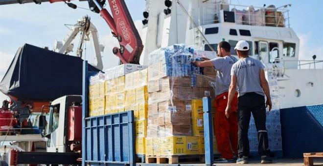 Operarios de Open Arms supervisan la carga de ayuda humanitaria al buque tras recibir la autorización para zarpar del puerto de Barcelona./ Alejandro García (EFE)