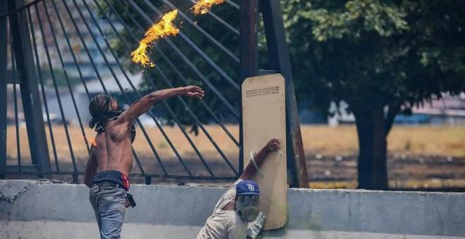 Opositores se enfrentan con la policía en una manifestación este miércoles en las calles de Caracas (Venezuela). /EFE