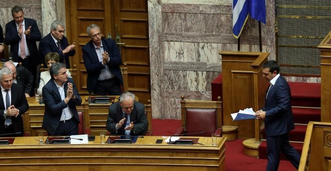 El primer ministro griego, Alexis Tsipras, recibe un aplauso de los ministros de su gobierno tras un discurso durante una sesión parlamentaria. | Reuters