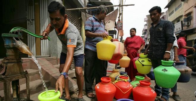 Un hombre usa una bomba manual para llenar un recipiente con agua potable mientras otros esperan en una cola en una calle de Chennai./ REUTERS