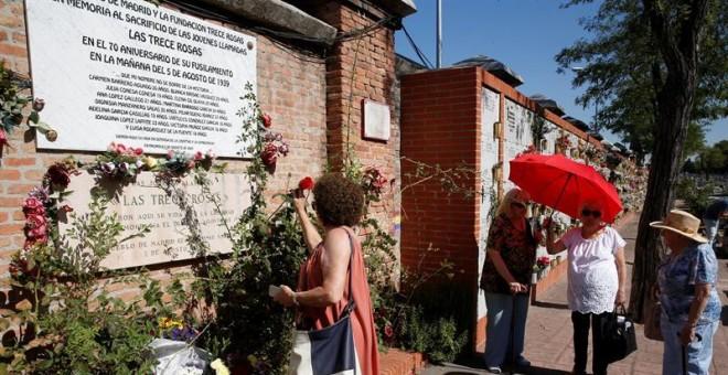 Una mujer coloca una rosa en el muro dedicado a las 13 jóvenes republicanas en el homenaje convocado por el PCE. / EFE