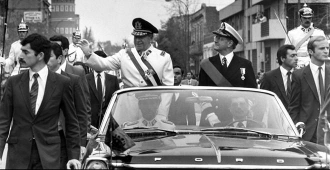 El general Augusto Pinochet (l), jefe de la junta militar chilena, saluda el 11 de septiembre de 1973 en Santiago, poco después de la muerte del presidente Allende, elegido en las urnas.- AFP