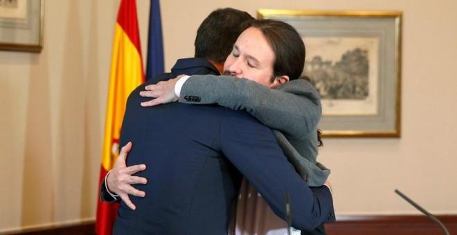 El presidente del Gobierno español en funciones, el socialista Pedro Sánchez, de espaldas, y el líder de Unidas Podemos, Pablo Iglesias, se abrazan en el Congreso de los Diputados donde firmaron un acuerdo para la formación de un Ejecutivo en España tras