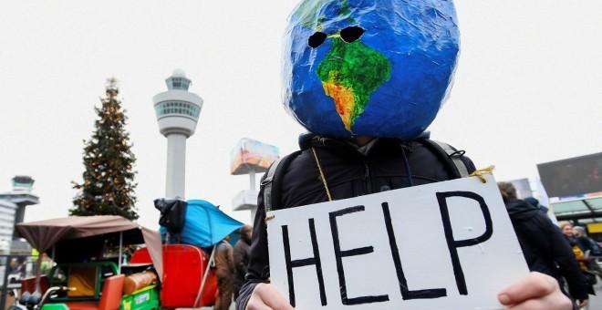 Un manifestante disfrazado de planeta Tierra sujeta un cartel en el que se puede leer 'ayuda'. REUTERS/Piroschka van de Wouw