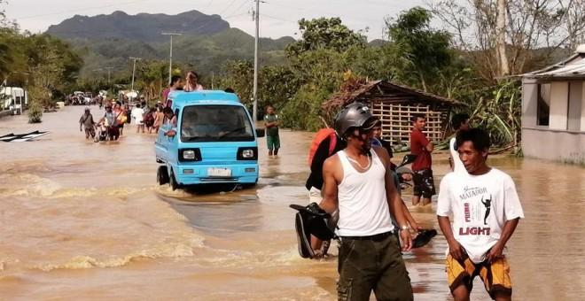 Ormoc (Filipinas), 25/12/2019.- Gente anda por el agua en una carretera inundada el día de Navidad en la ciudad de Ormoc, Filipinas, azotada por el tifón Phanfone, el 25 de diciembre de 2019. El tifón Phanfone (conocido localmente como Ursula) tocó tierra
