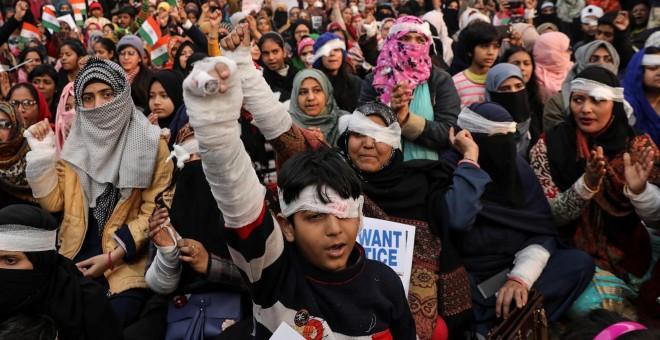 Los manifestantes tienen los ojos cubiertos con un parche durante una protesta para mostrar solidaridad con el estudiante universitario Jamia Millia Islamia que presuntamente perdió el ojo durante las protestas contra la nueva ley de ciudadanía, en Nueva