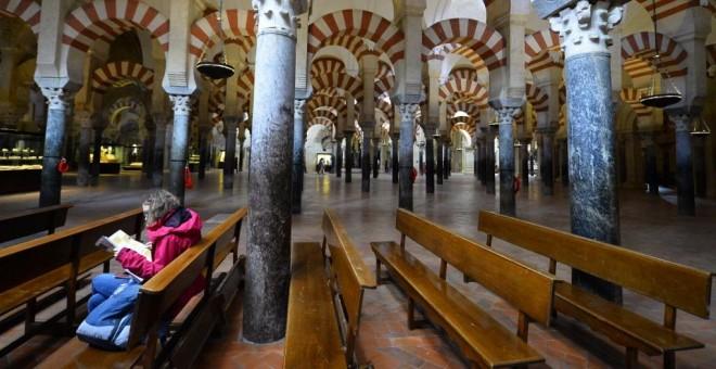 Una turista leen sentada en la Mezquita de Córdoba. AFP/Jorge Guerrero
