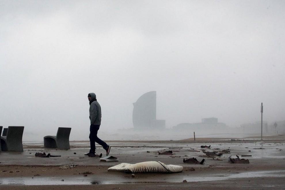 21/01/2020.- Una persona camina por la playa de la Barceloneta, en Barcelona durante el temporal. / EFE - ENRIC FONTCUBERTA