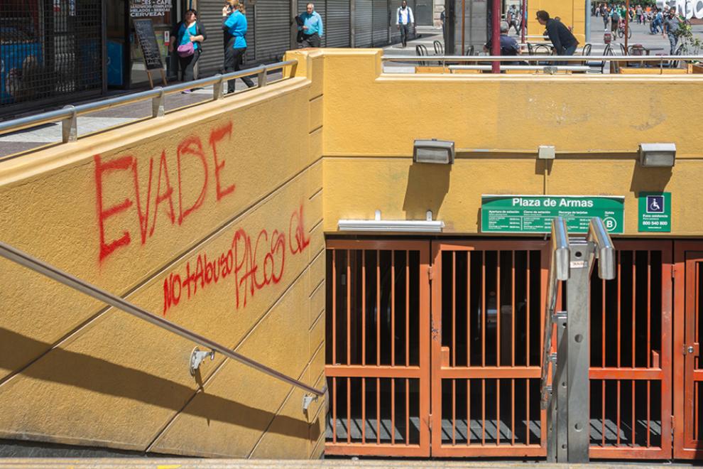 """Entrada a la estación de la Plaza de Armas del Metro de Santiago cerrada. Una pintada llama a la evasión, """"No más abuso"""". – Carlos Figueroa (WikiCommons)."""