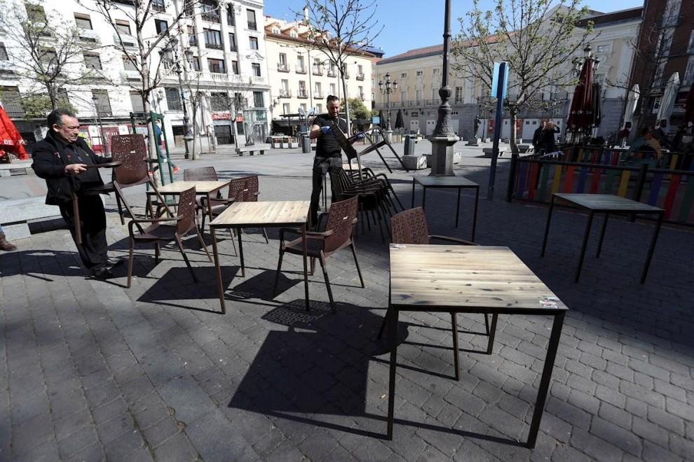 Varias personas recogen este viernes la terraza de un bar en la Plaza de Santa Ana, en el centro de Madrid. - EFE