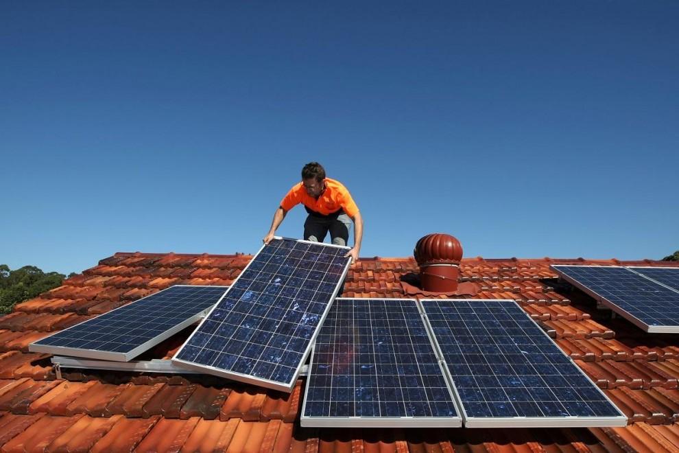 Un operario trabaja colocando paneles solares en un tejado de una vivienda.