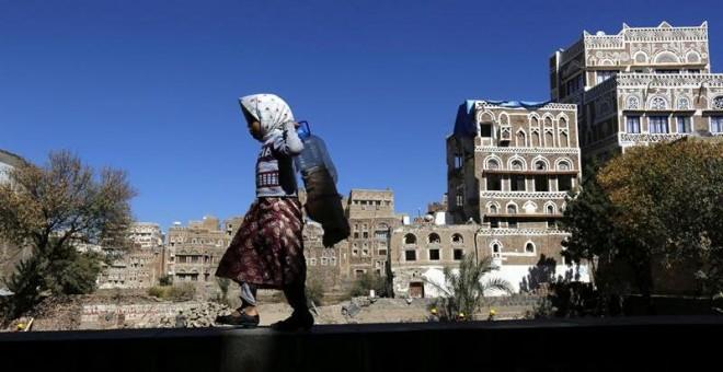 Una niña camina junto a edificios históricos destruidos por los bombardeos de la coalición árabe liderada por Arabia Saudí en Saná, Yemen. Las autoridades del país planean la reconstrucción de dos edificios destruidos el pasado 12 de junio. La Organizació