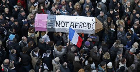"""Citizens carrying a giant cardboard pencil reading """"Not Afraid"""" take part in a Hundreds of thousands of French citizens solidarity march (Marche Republicaine) in the streets of Paris January 11, 2015. French citizens will be joined by dozens of foreign le"""