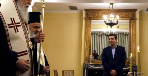 El nuevo primer ministro griego, Alexis Tsipras, observa a los sacerdotes ortodoxos que intervienen en la ceremonia de juramiento de los nuevos miembros del Gobierno heleno. REUTERS/Yannis Behrakis