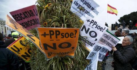 Una mujer coloca unas pancartas en un arbusto durante las Marchas de la Dignidad. REUTERS / Sergio Pérez