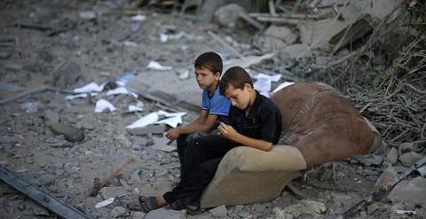 Niños palestinos tras un bombardeo de Israel. REUTERS