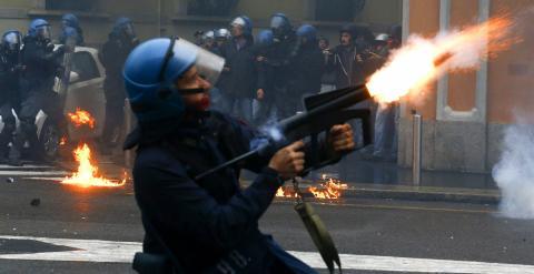 Un policía antidisturbios lanza gases lacrimógenos. - REUTERS