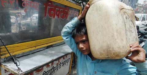 Sachin, de nueve años, carga con un recipiente con agua para el puesto de comida en el que trabaja Amritsar. AFP/Narinder NANU