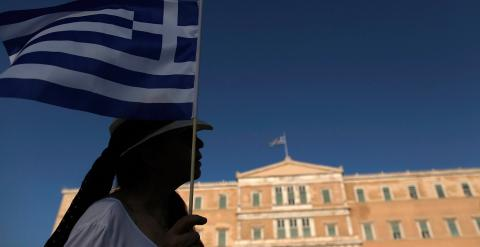 Una manifestante sostiene una bandera griega en frente del Parlamento.-Yannis Kolesidis (EFE)
