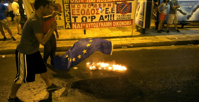 An anti-austerity demonstrator throws a European Union flag into a fire in front of the parliament in Athens, Greece July 22, 2015. Greek Prime Minister Alexis Tsipras sought on Wednesday to contain a rebellion in his left-wing Syriza party ahead of a vot