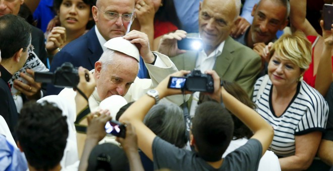 Pope Francis wears a skull cap he received from a faithful as he arrives to lead his Wednesday general audience in Paul VI hall at the Vatican Pope Francis wears a skull cap he received from a faithful as he arrives to lead his Wednesday general audience