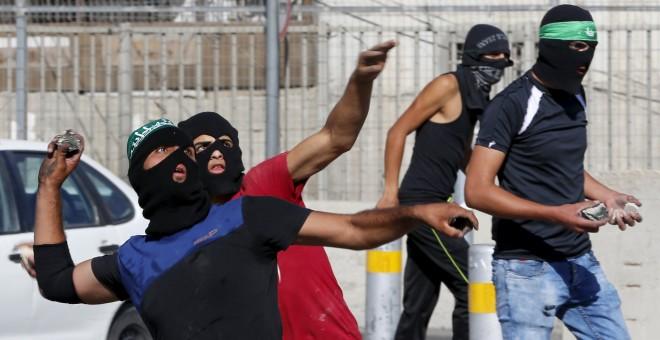 Los palestinos lanzan piedras hacia la policía fronteriza israelí durante los enfrentamientos en un puesto de control entre el campamento de refugiados de Shuafat y Jerusalén./ REUTERS/ Ammar Awad