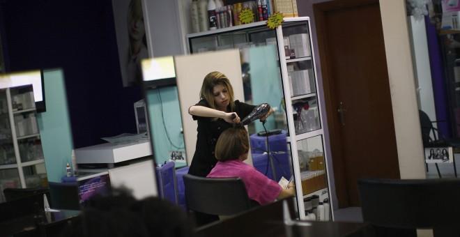 Una peluquera atiende a una clienta en un local de Ronda, Málaga. /REUTERS