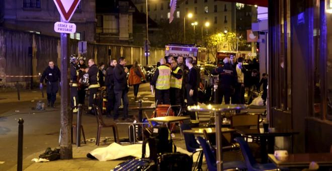 Los servicios de rescate cerca de los cuerpos cubiertos fuera de un restaurante Tras un tiroteo en París, Francia, 13 de noviembre de 2015. REUTERS / Philippe WOJAZER