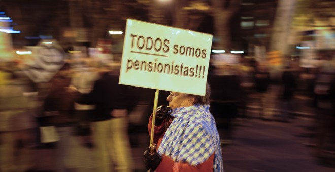 Una anciana con una pancarta que dice 'Todos somos pensionistas', en una manifestación contra las medidas del Gobierno. AFP / Pedro Armeste