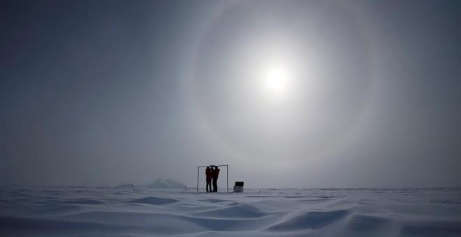 Imagen tomada el 18 de noviembre de 2015 que muestra a dos científicos midiendo la radiación solar y su albedo en el campamento Glaciar Union, a 1000 km del Polo Sur. Investigadores de la Universidad de Santiago de Chile informaron hoy que en los primeros