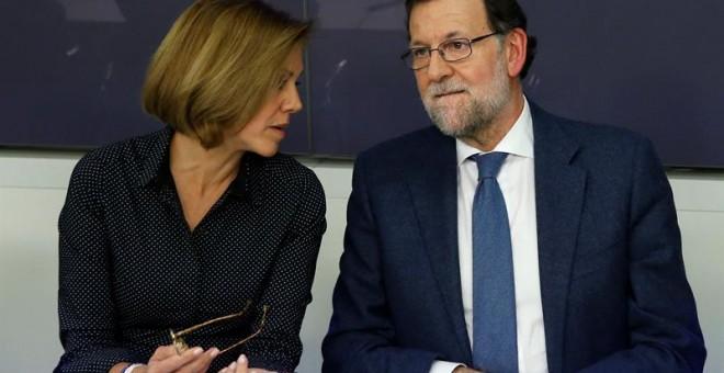 El presidente del Gobierno, Mariano Rajoy, conversa con la secretaria general del PP, María Dolores de Cospedal, durante la reunión de la Junta Directiva Nacional del PP celebrada en la sede del partido en Madrid, para aprobar las propuestas de los candid