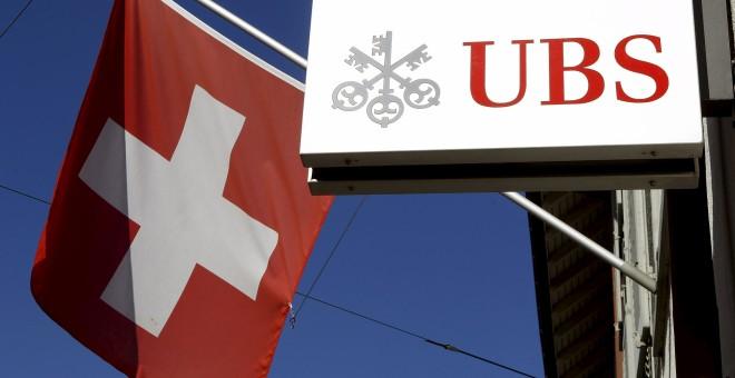 Foto de la bandera nacional de Suiza al lado del logotipo del banco suizo UBS en la ciudad de Riehen. REUTERS