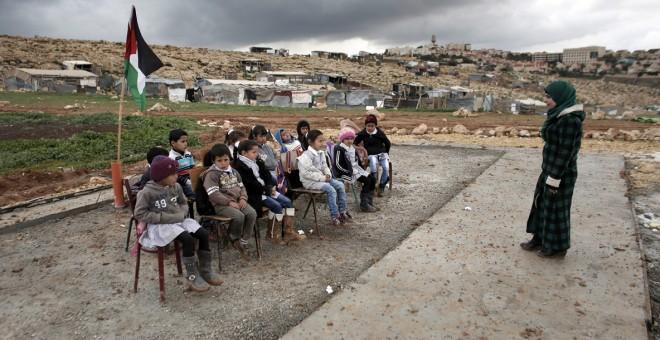 Una maestra palestina durante una clase a niños en la comunidad de Abu Nawar cerca del asentamiento judío de Maale Adumim, en la ciudad cisjordana de Al-Azariya, al este de Jerusalén. AHMAD GHARABLI / AFP