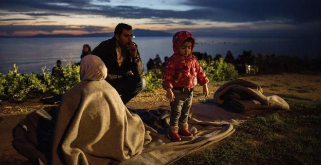 Una familia de refugiados descansa tras llegar a la isla de Lesbos tras cruzar el mar desde Turquía en el puerto de Mytilene (Grecia) hoy, 9 de marzo de 2016. EFE/Kay Nietfeld